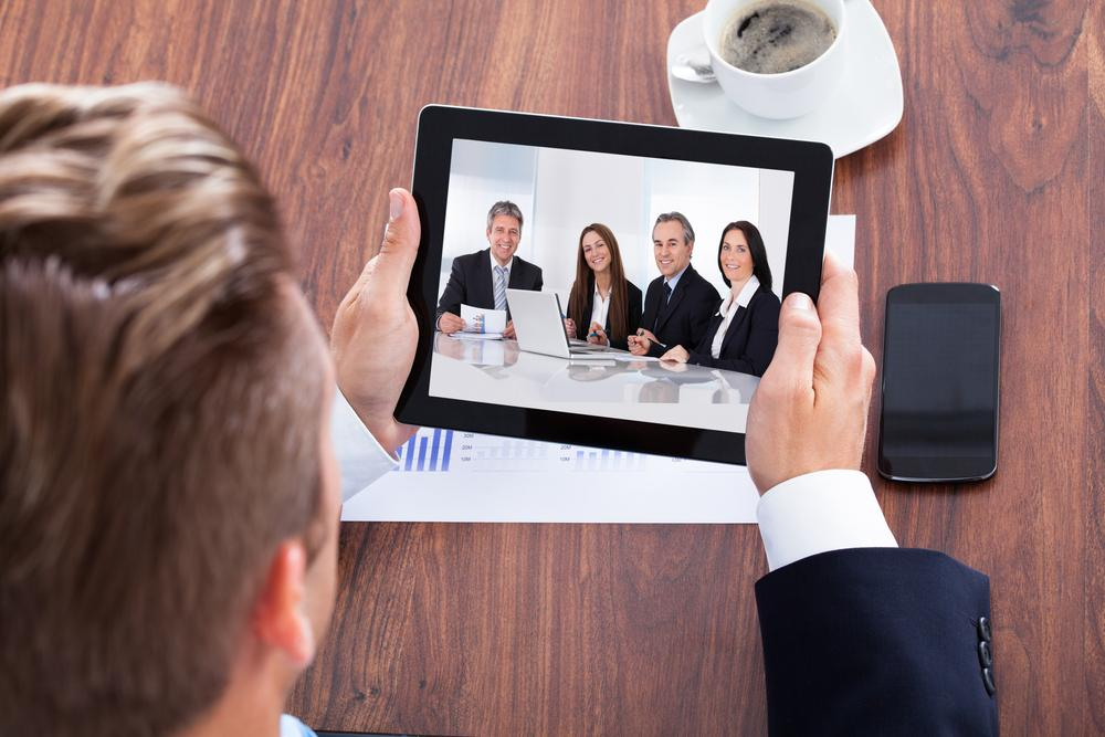 businessman on a video conference holding a tablet