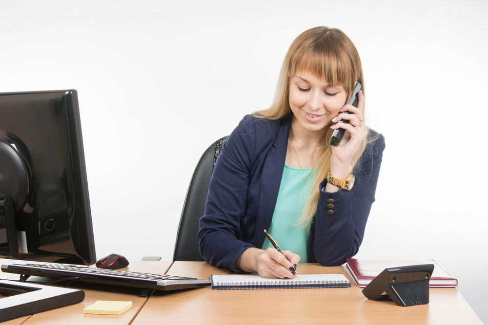 businesswoman taking down notes while on the phone